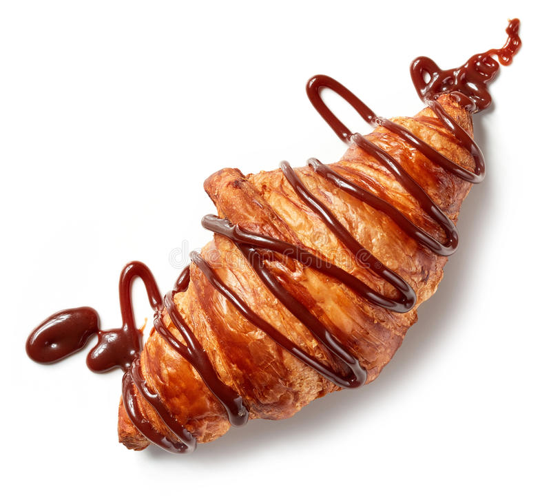 Freshly baked croissant decorated with chocolate sauce royalty free stock image