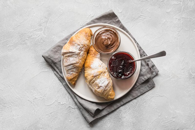 Freshly baked croissants with berry jam on gray. Top view. Freshly baked croissants with berry jam on gray background. Top view royalty free stock photo