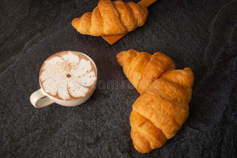 Freshly baked croissants on a black background with a white coffee cup,breakfast bread brown beverage morning,Concept: meal royalty free stock photography