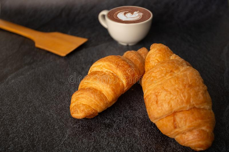 Freshly baked croissants on a black background with a white coffee cup,breakfast bread brown beverage morning,Concept: meal royalty free stock photos