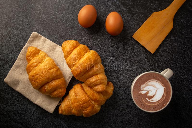 Freshly baked croissants on  black background with a white coffee cup,breakfast bread brown beverage morning,Concept: meal stock image