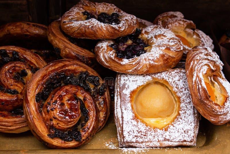 Freshly baked danish pastries, custard, apricots, raisins, cinnamon swirl dusted in icing sugar and glaze. Freshly baked danish pastries, custard, apricots royalty free stock photos