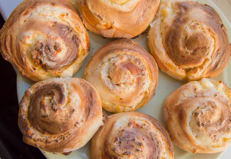 Freshly baked delicious cinnamon rolls on a plate, top view. Sweet homemade Christmas pastries in the form of rolls.  royalty free stock photo