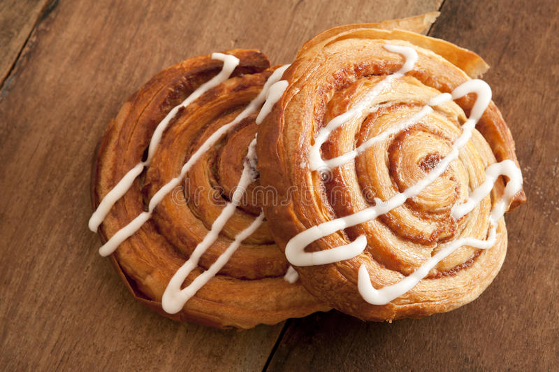 Freshly baked flaky Danish pastries. Freshly baked spiral Danish pastries with flaky puff pastry filled with apple or almond paste and drizzled with white icing royalty free stock photo