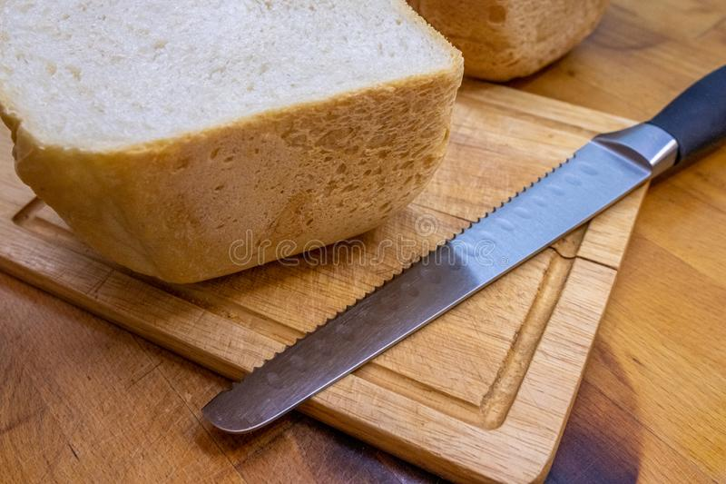 Freshly baked homemade bread cut in half on a wooden kitchen board and lying next to a bread knife for cutting bread royalty free stock images