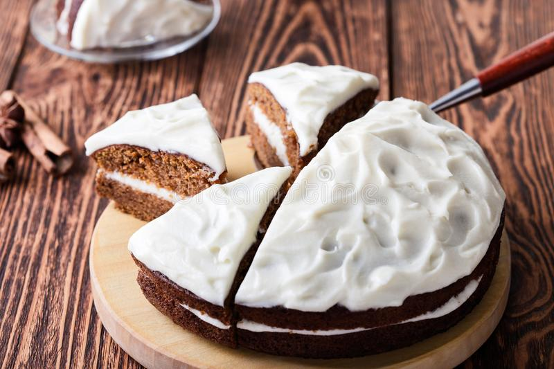 Butternut squash cake with cream cheese frosting. Freshly baked homemade butternut squash cake with cream cheese frosting on rustic wooden board, sliced and stock photo