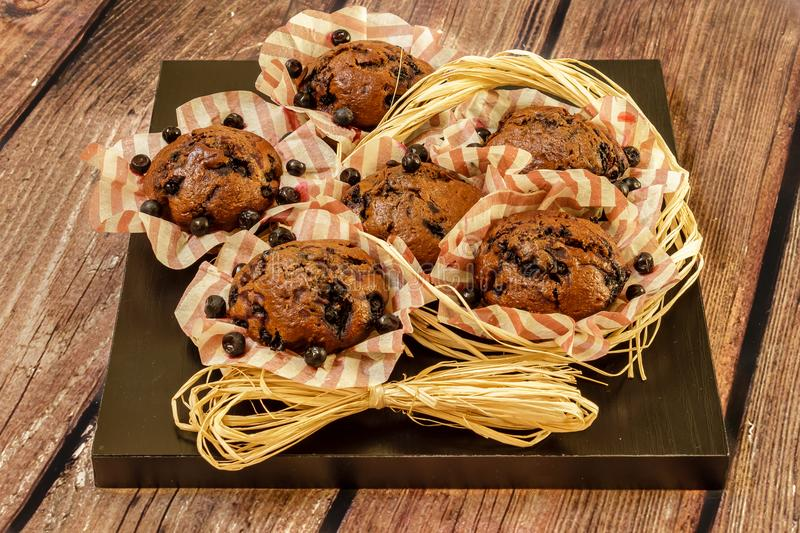 Freshly baked homemade muffins with blueberries on a black wooden plate royalty free stock photography