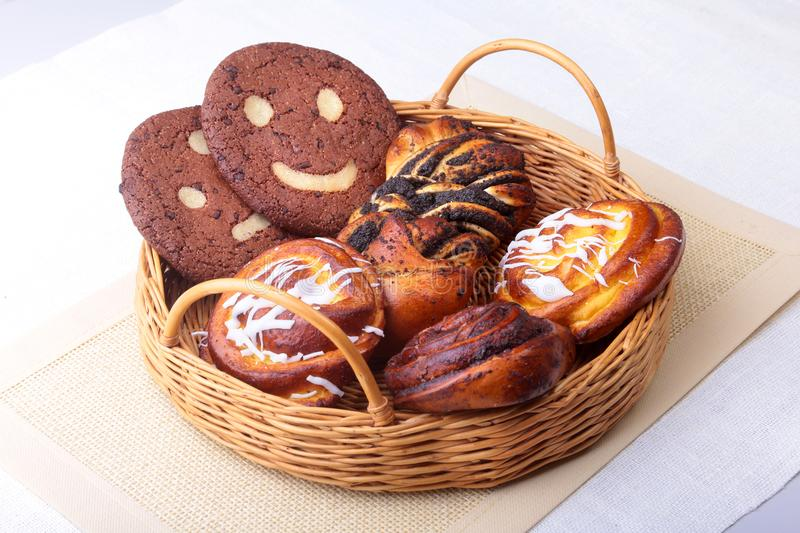 Freshly baked homemade sweet rolls with cinnamon, oatmeal cookies in a wicker basket. Healthy Food Snack Concept. Copy stock images