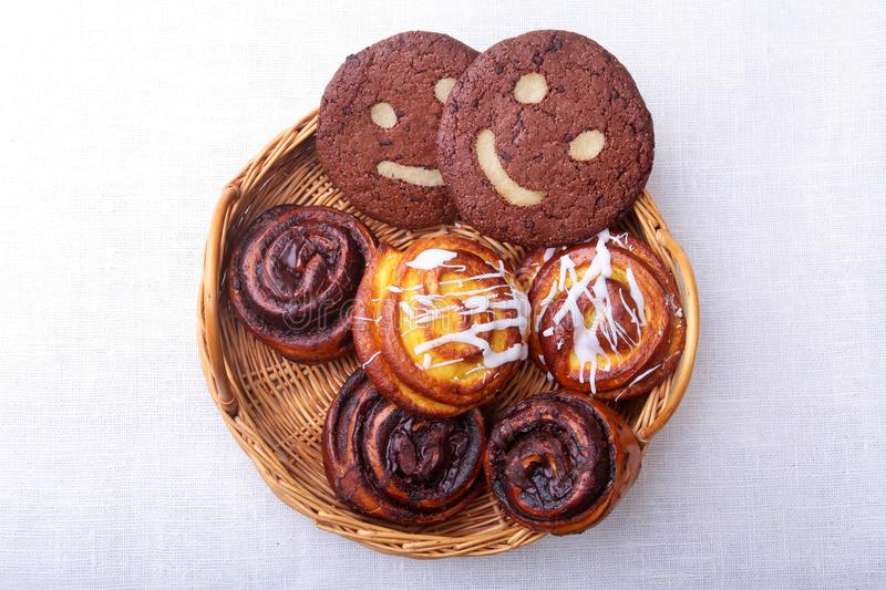 Freshly baked homemade sweet rolls with cinnamon, oatmeal cookies in a wicker basket. Healthy Food Snack Concept. Copy stock photos