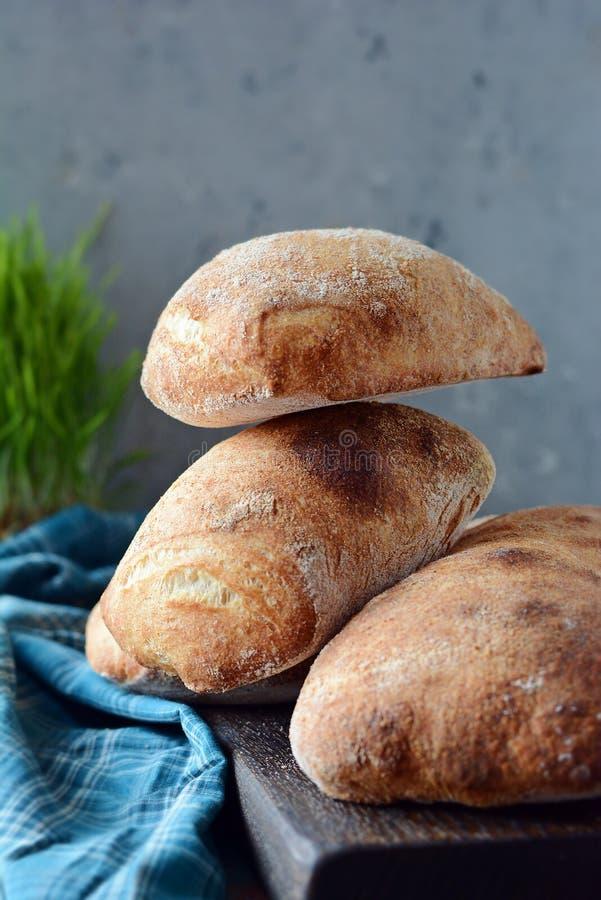 Freshly baked Italian ciabatta bread on wooden cutting board. royalty free stock image