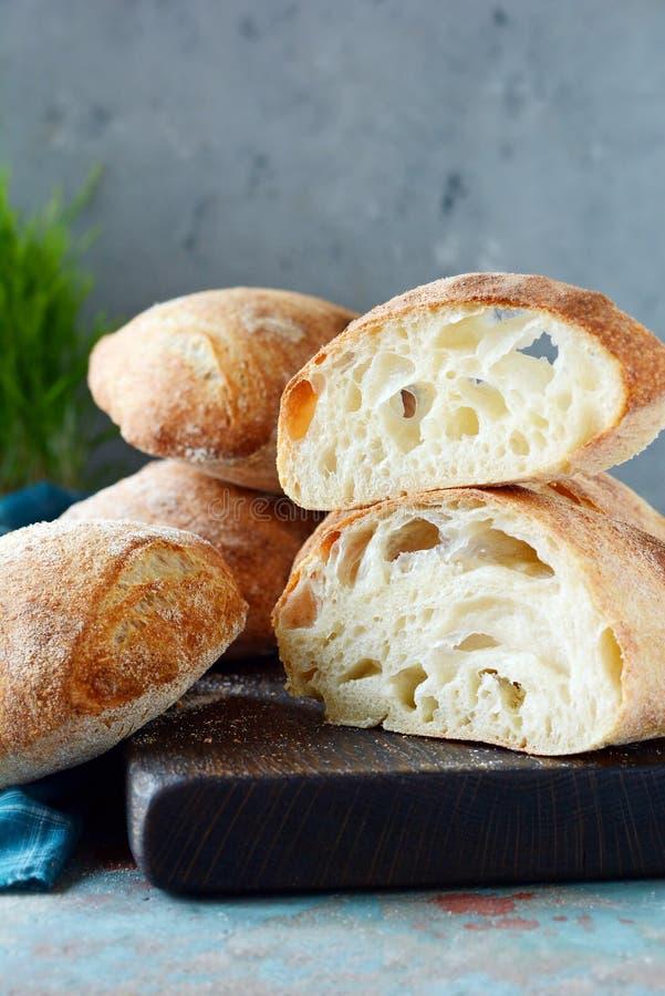 Freshly baked Italian ciabatta bread on wooden cutting board. stock images