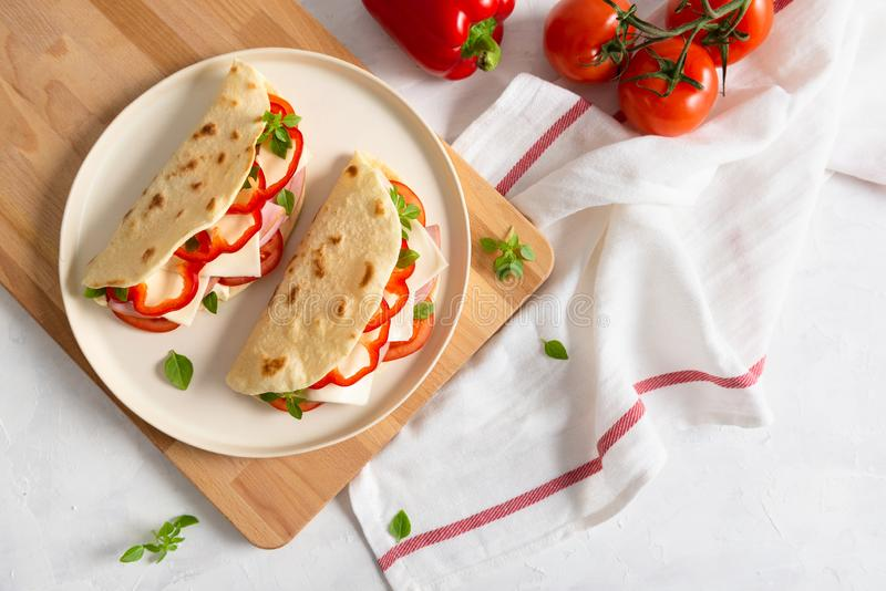 Freshly baked italian piadina with cheese, tomato, ham, red pepper and basilio on a white plate on a white wooden table. Top view royalty free stock photo