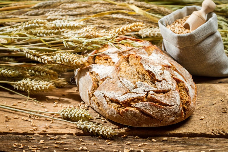 Freshly baked loaf of bread and a bag with grains royalty free stock photos
