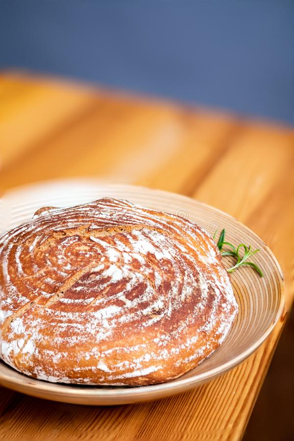 Freshly baked loaf of bread with rosemary garnish stock photo