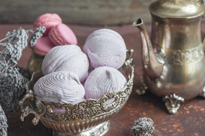 Freshly baked marshmallows and macaroons on metal plate with small white flowers and tea appliances composition on wooden backgrou stock image