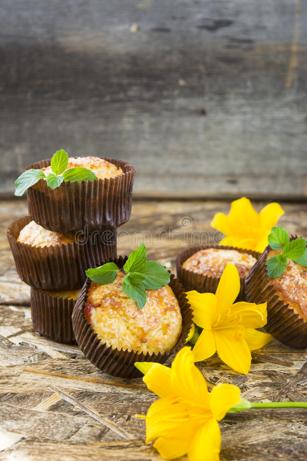 Freshly baked muffins with plum, mint and lily flower stock images