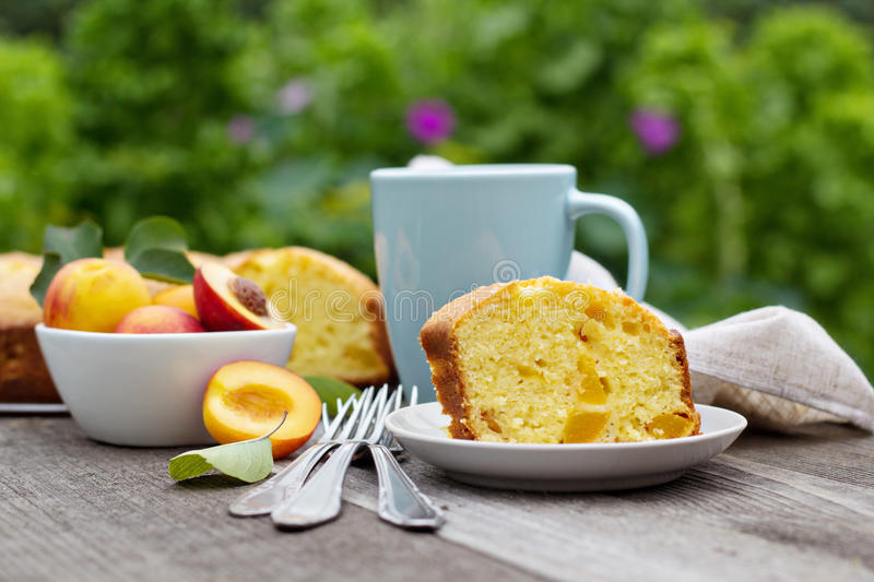 Freshly baked peach cake with tea stock image