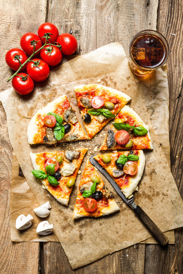 Freshly baked pizza served with a cold drink royalty free stock images