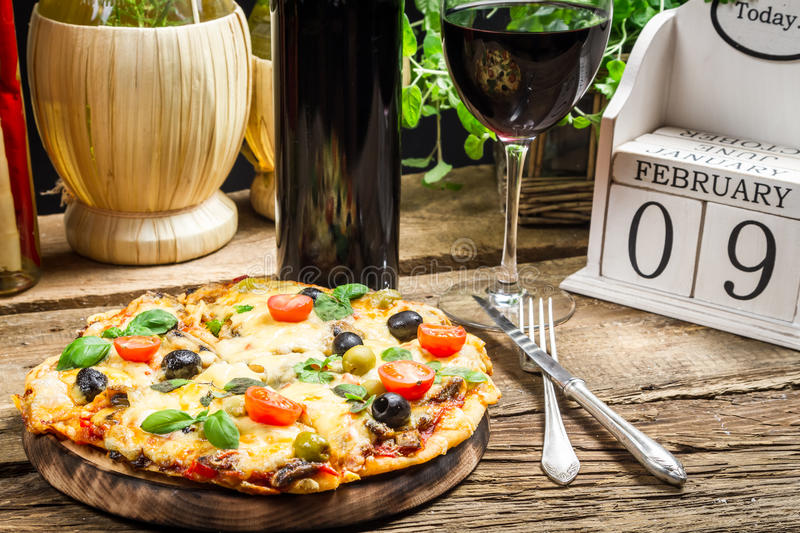 Freshly baked pizza served with wine on a calendar background royalty free stock images