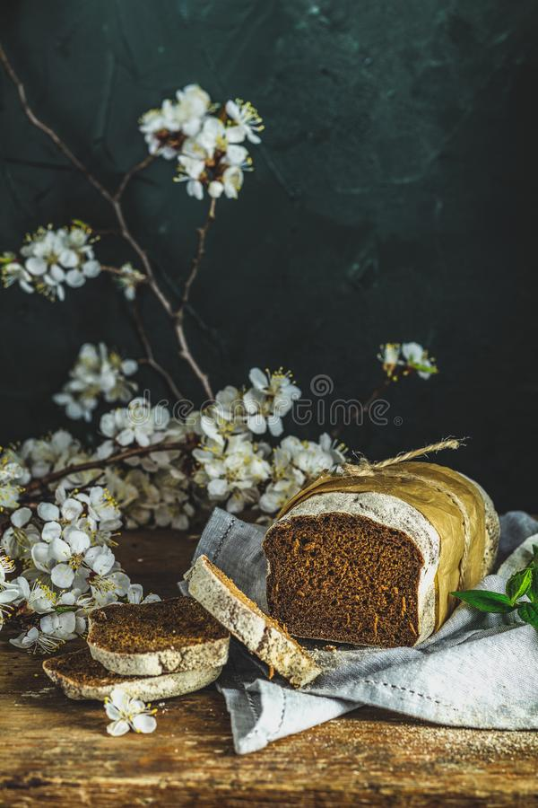 Freshly baked rye handmade breads on old wooden table with linen napkin and apricot tree blossom branch royalty free stock photography