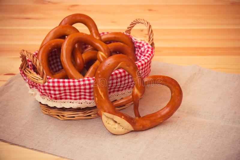 Freshly baked salted soft pretzels in wicker basket on wooden table stock photography
