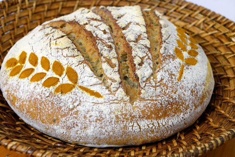 Sourdough bread decorated with wheat spice in a basket royalty free stock photos