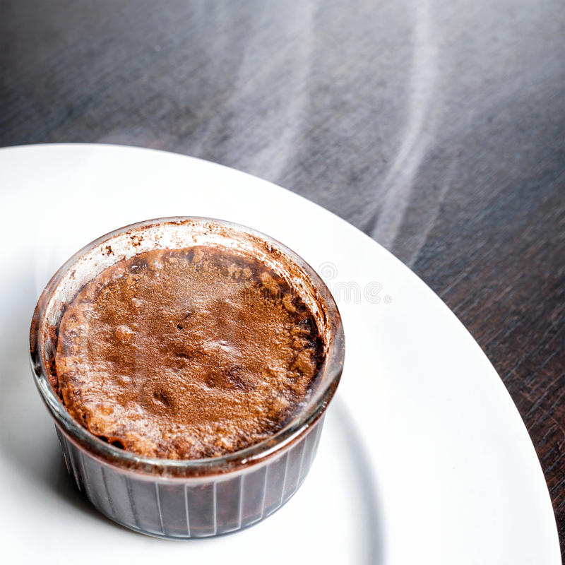 Freshly baked steaming hot dessert chocolate fondant lava cake served on white plate. Famous French dessert on dark wooden table t. Op view stock photo