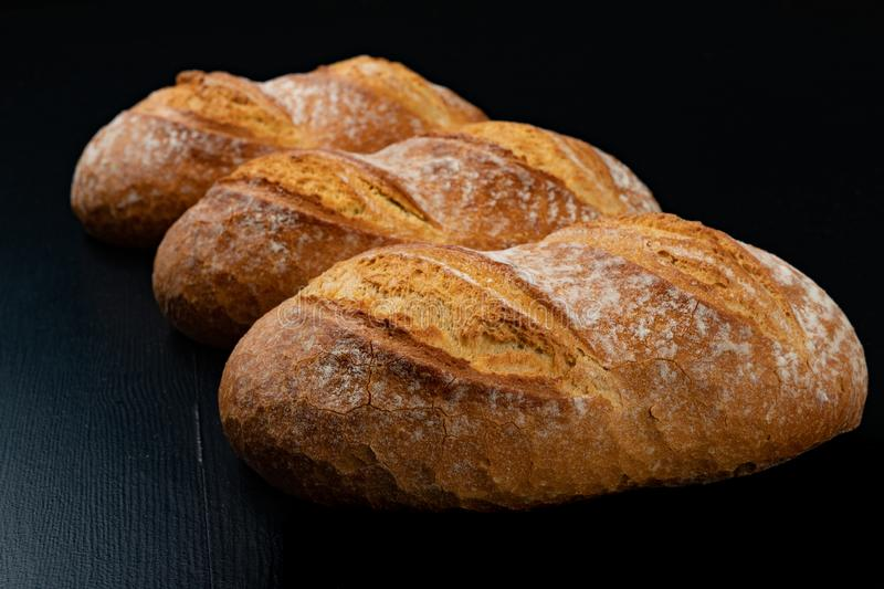 Freshly baked tasty bread on a dark table. Tasty baked goods straight from the bakery. Black background, artisan, beautiful, brown, chalkboard, close-up royalty free stock image