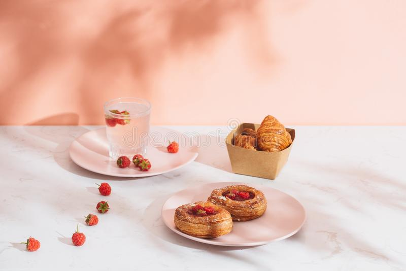 Freshly baked traditional pastry sweet mini danish raspberry and raspberries soda drinks.  royalty free stock images