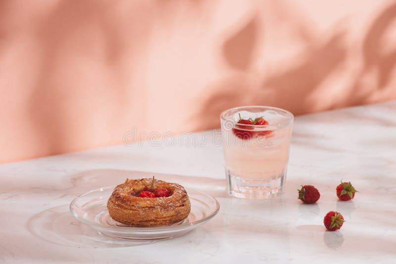 Freshly baked traditional pastry sweet mini danish raspberry and raspberries soda drinks.  royalty free stock photo