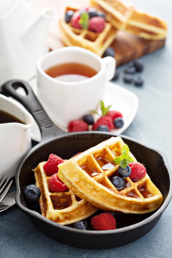 Freshly baked waffles with berries for breakfast. Freshly baked waffles with berries and tea for breakfast stock photography