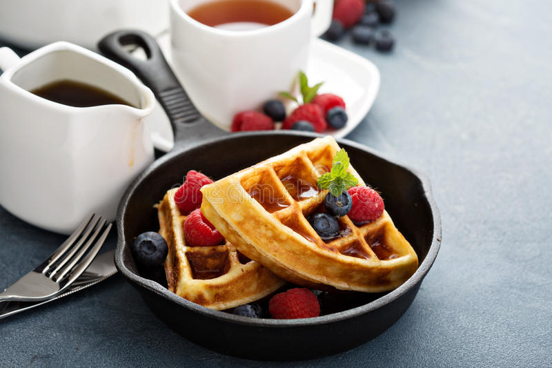 Freshly baked waffles with berries for breakfast. Freshly baked waffles with berries and tea for breakfast stock photos