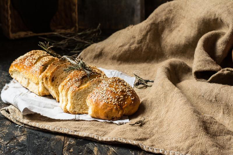 Freshly baked wheat bread on natural linen napkin and bag. Homemade bakery. Still life of bread. Slice of gold rustic crusty loave royalty free stock photography