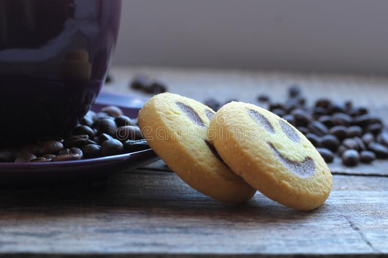 Freshly brewed coffee in a violet cup with cookies on the background of coffee beans royalty free stock photos