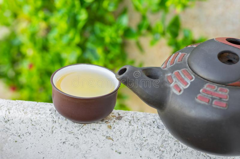 Freshly brewed green tea in clay cup pot on stone in garden nature foliage background. Chinese Japanese Asian Cuisine stock photo