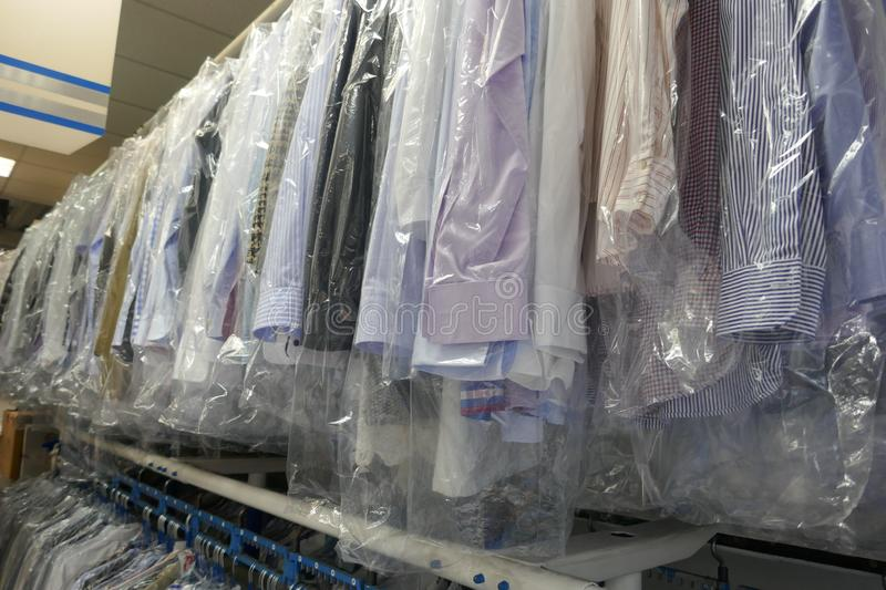 Freshly cleaned men`s shirts and ladies blouses in a textile cleaning royalty free stock photography