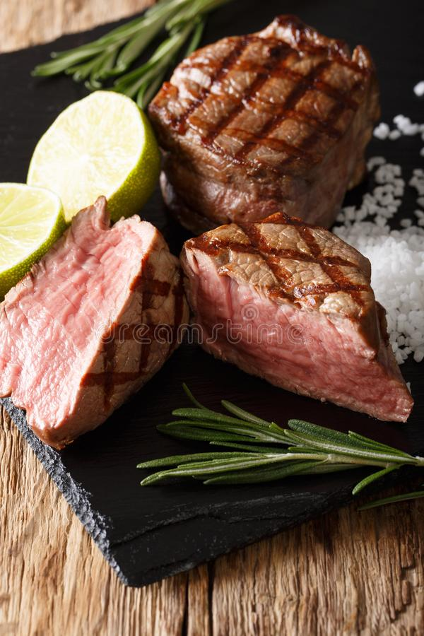 Freshly cooked mignon fillet steak with lime and rosemary close-up. vertical stock images
