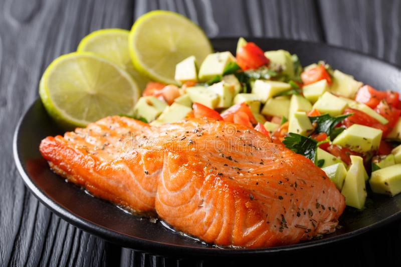 Freshly cooked salmon steak with lime, avocado and tomatoes close-up. horizontal royalty free stock images