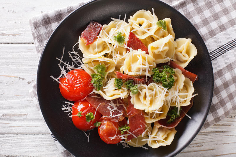 Freshly cooked tortellini with prosciutto and parmesan on a plat royalty free stock image