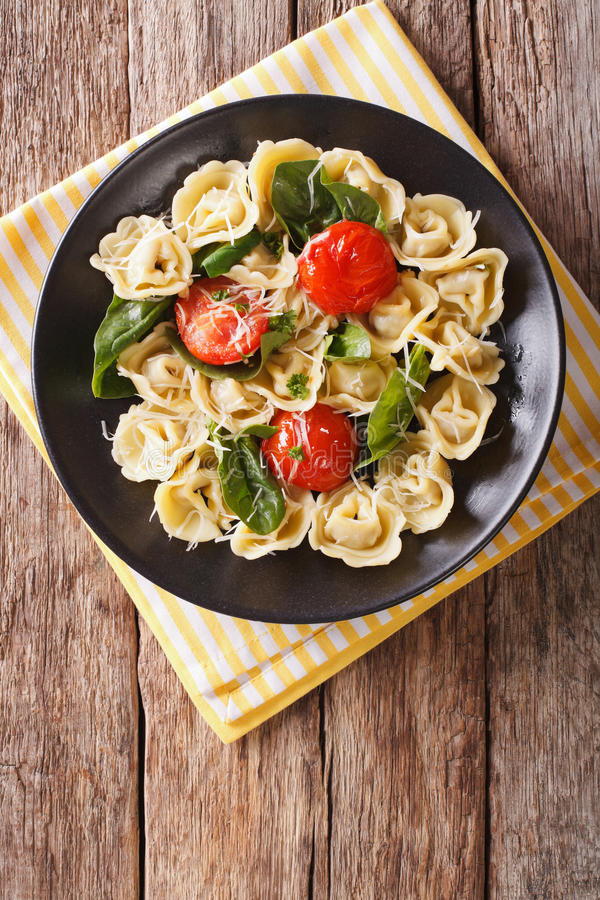 Freshly cooked tortellini with spinach and parmesan on a plate. stock images