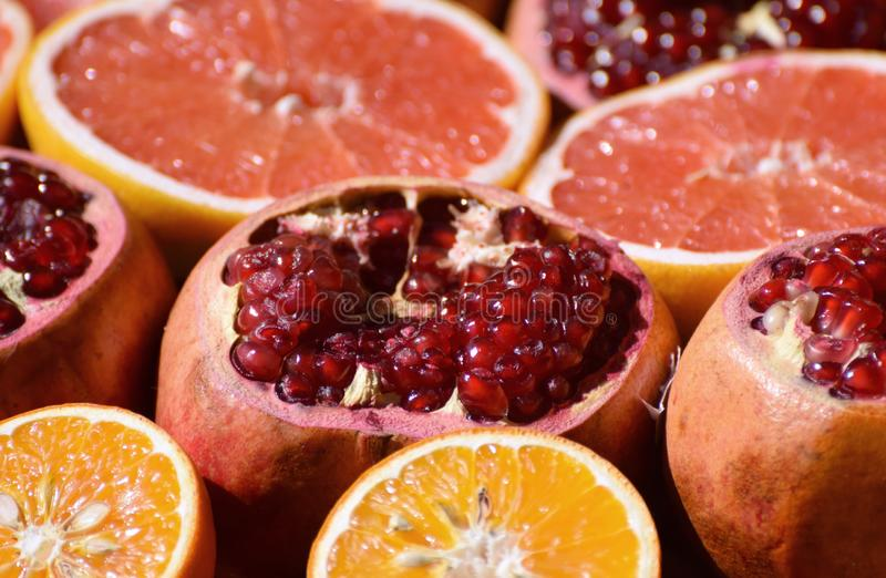 Pomegranates and oranges. Fresh fruits. Freshly cut pomegranates and citrus fruit for making juice on a market stall stock photo