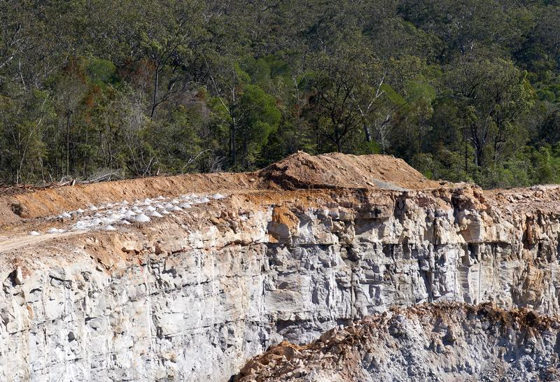 Freshly drilled holes atop the working-face of a rock and gravel quarry. royalty free stock photo