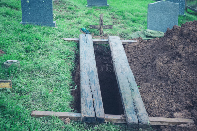 Freshly dug grave. A freshly dug open grave in a cemetery stock images