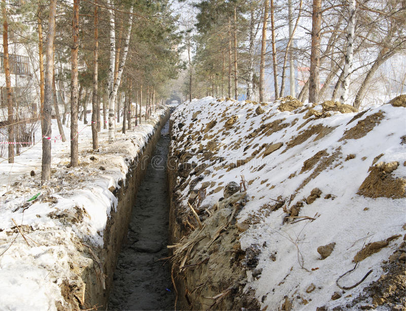 Freshly dug trench. Earthworks.Dug trench and bunch of dug ground,powdered with snow royalty free stock image