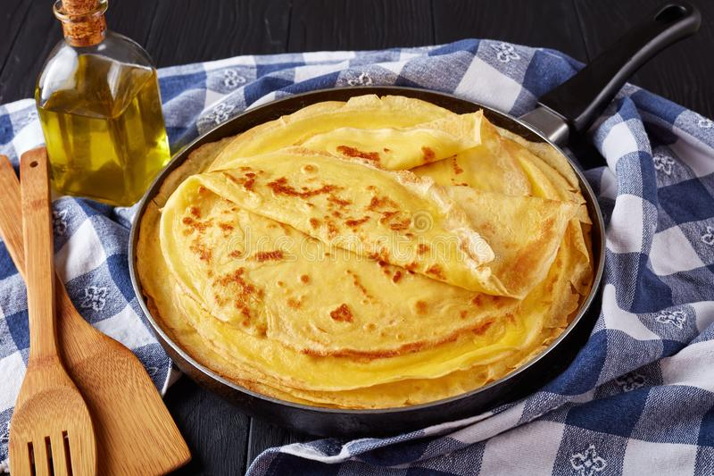 Freshly fried hot french crepes, close-up. Freshly fried homemade french crepes on a skillet on black wooden table with kitchen towel, horizontal view from above royalty free stock photography