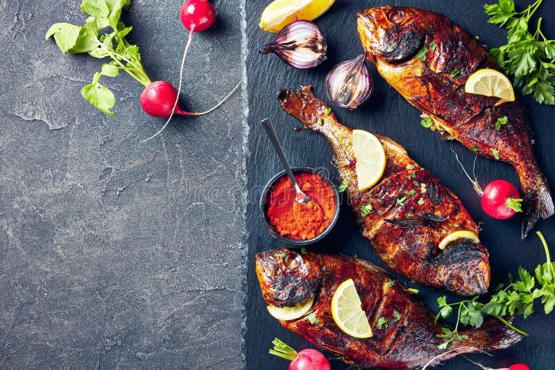 Freshly grilled dorado fish on a black tray stock photography