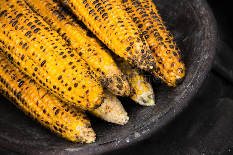 Freshly grilled sweet corns served on a rustic clay bowl royalty free stock photos