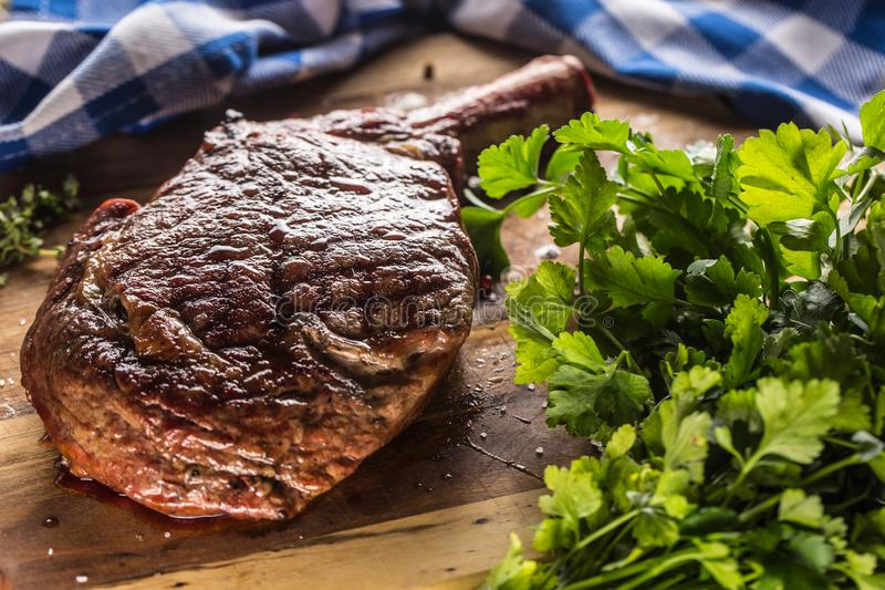 Freshly grilled tomahawk steak on slate plate with salt pepper rosemary and parsley herbs stock photo