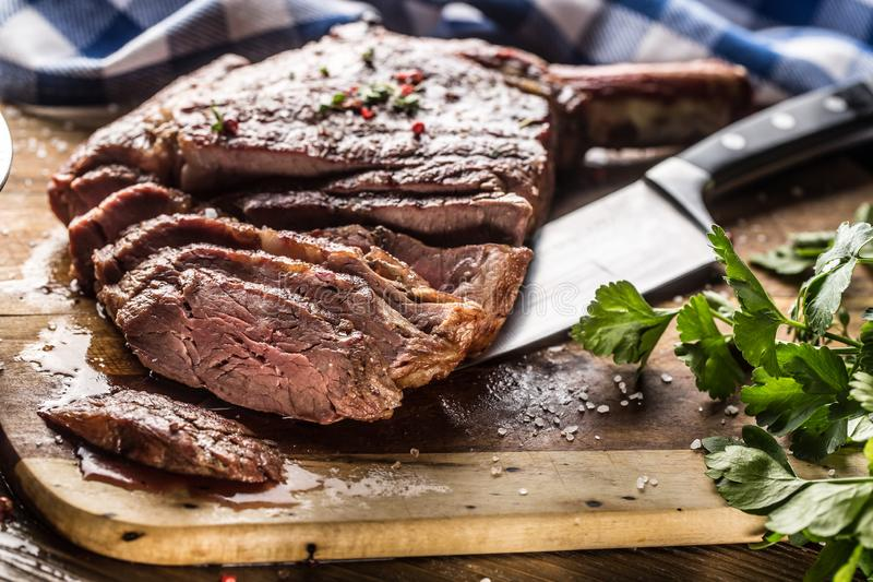 Freshly grilled tomahawk steak on slate plate with salt pepper rosemary and parsley herbs. Sliced pieces of juicy beef steak.  stock image