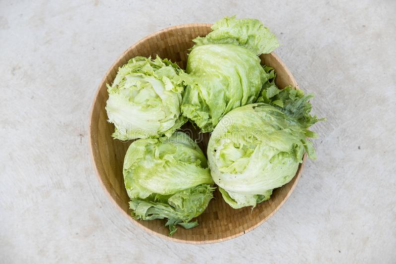 Iceberg lettuce in wooden bowl stock images